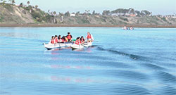 groups on people on two kayaks on the ocean in Newport Bay with mountains and blue sky