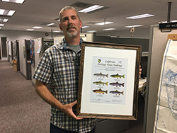 Man wearing gray plaid shirt holding frame with certificate depicting trout standing in office.