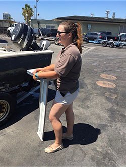 Woman standing in parking lot next to outboard motor boat on trailer