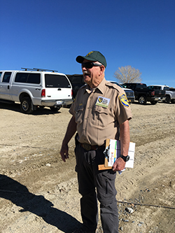 Man wearing CDFW uniform, sunglasses, and green ball cap standing in dirt parking lot holding clipboard.