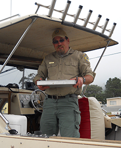 Man standing on boat under roof holding metal clipboard.