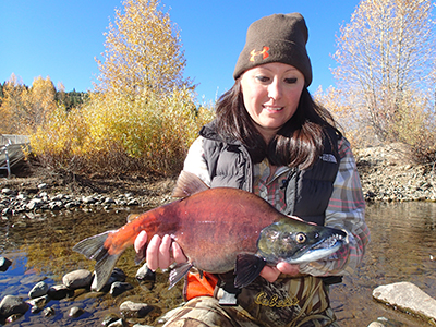 Woman wearing brown beanie cap, black puffy vest, flannel shirt, and camo waders standing in streambed holding a salmon