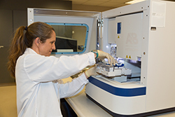 Woman with ponytail in hair wearing white laboratory coat with white latex gloves holding tray in front of a large machine.