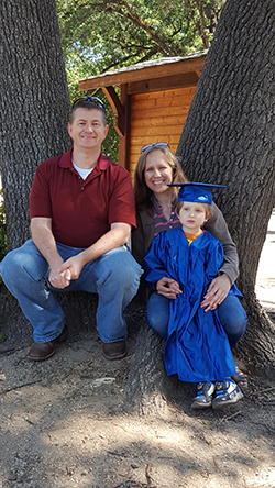 Smiling man wearing red shirt and blue jeans with smiling woman with arms around young child wearing blue graduation cap and gown in front of tree.