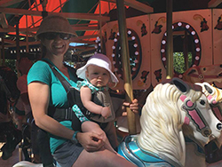 Smiling woman wearing wide brim hat, sunglasses, shorts and blue tshirt on merry go round horse holding baby in front facing baby carrier