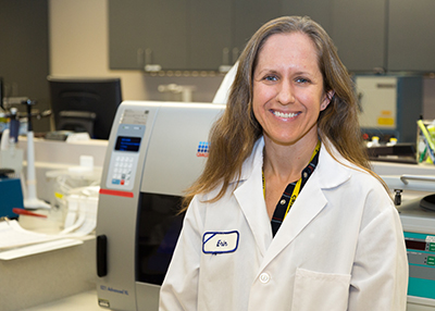 Smiling woman with long brown hair wearing white laboratory coat in laboratory with machines in background.
