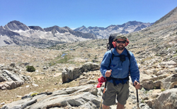 Bearded man wearing blue windbreaker, gray shorts, fishermans hat, sunglasses, and backpack while leaning on 2 hiking poles. Background is rocky and mountainous.