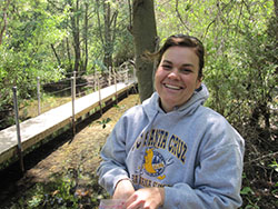 Smiling woman wearing grey sweatshirt outside in forested area with footbridge in background
