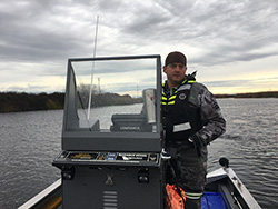 Man wearing gray camo foul weather gear, backward ball cap, and black life vest with yellow reflectors behind helm on fishing boat on water. Cloudy skies and grass-covered levy in background