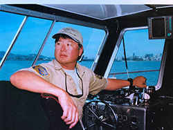 Man wearing beige official Department of Fish and Wildlife uniform with beige ball cap inside boat at helm.
