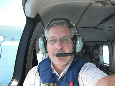 Man wearing glasses, blue life vest, and radio headset with microphone inside cabin of small airplane