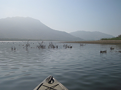Bow of kayak floating on calm lake with foggy mountains in background