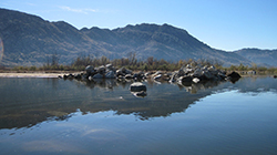 Calm lake facing a pile of large rocks partially submerged with mountains in the background