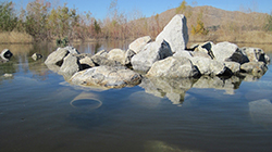 Lake with partially submerged pile of rocks with trees and mountain in the background