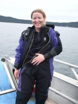 Smiling woman in black and purple scuba diving suit on boat on water. Land in background.