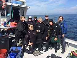 Group of eight smiling women in black scuba gear on boat on water.