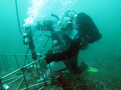 Scuba diver underwater holding large tool in one hand and large metal cage in other.