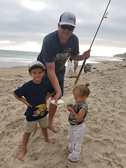 White male wearing blue t-shirt, ball cap, and sunglasses holding fishing rod in one hand and small fish in another standing on beach next to young girl and young boy. Overcast sky and water in background.