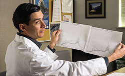 Man wearing white lab coat holding up two sheets of white paper with graphs.