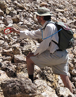 Man wearing beige fishing hat, khaki pants, white long sleeved shirt, and backpack on rocky slope holding round red item