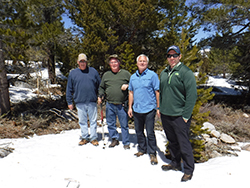 Four men standing next to each other with snow on the ground and trees in the background