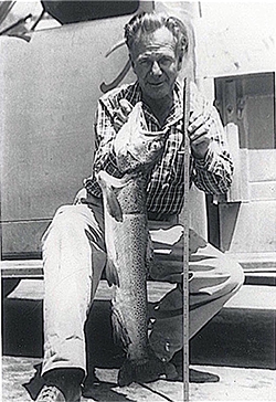 Black and white image of a man crouched in front of truck, holding a large fish in one hand and measuring stick in other hand. Man is wearing plaid collared shirt and pants.