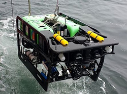 Black and green machine with two yellow tanks on top above water, suspended by chain.