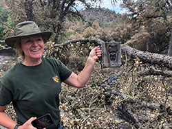 Woman in green shirt and green fishing hat holding up burned electronic box with fallen tree and trees in background.
