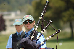 Woman in blue shirt and black vest with green ball cap holding bagpipes.
