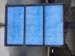 Large blue mat framed into 3 sections with black and orange rope handle on side.