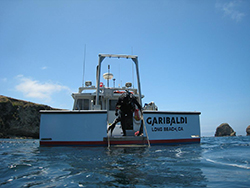 Scuba diver standing on stern of boat called the Garibaldi from Long Beach California