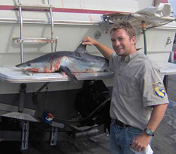 Smiling man wearing khaki shirt with CDFW arm patch with hand on dorsal fin of small shark on stern of boat.