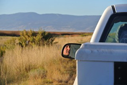 partial view of white pickup truck with face in sideview mirror. Grassland and mountain in background