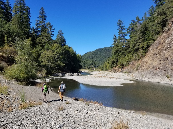 Two people walking along the South Fork Eel River.
