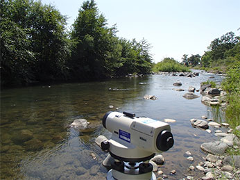 survey autolevel in Mill Creek and a stadia rod measuring water surface elevation  in Auburn Ravine