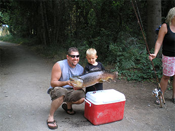 A young angler helps hold his catch of the day