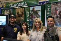 CDFW staff, including a game warden, in front of a CDFW themed booth
