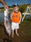 little boy stands next to catfish that is as long as he is tall