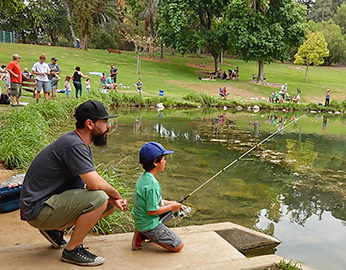 Child fishing with adult at urban pond