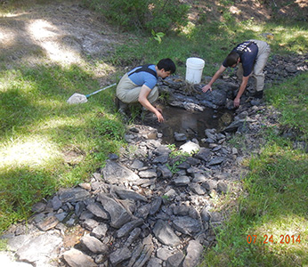 two men working in rocky streambed