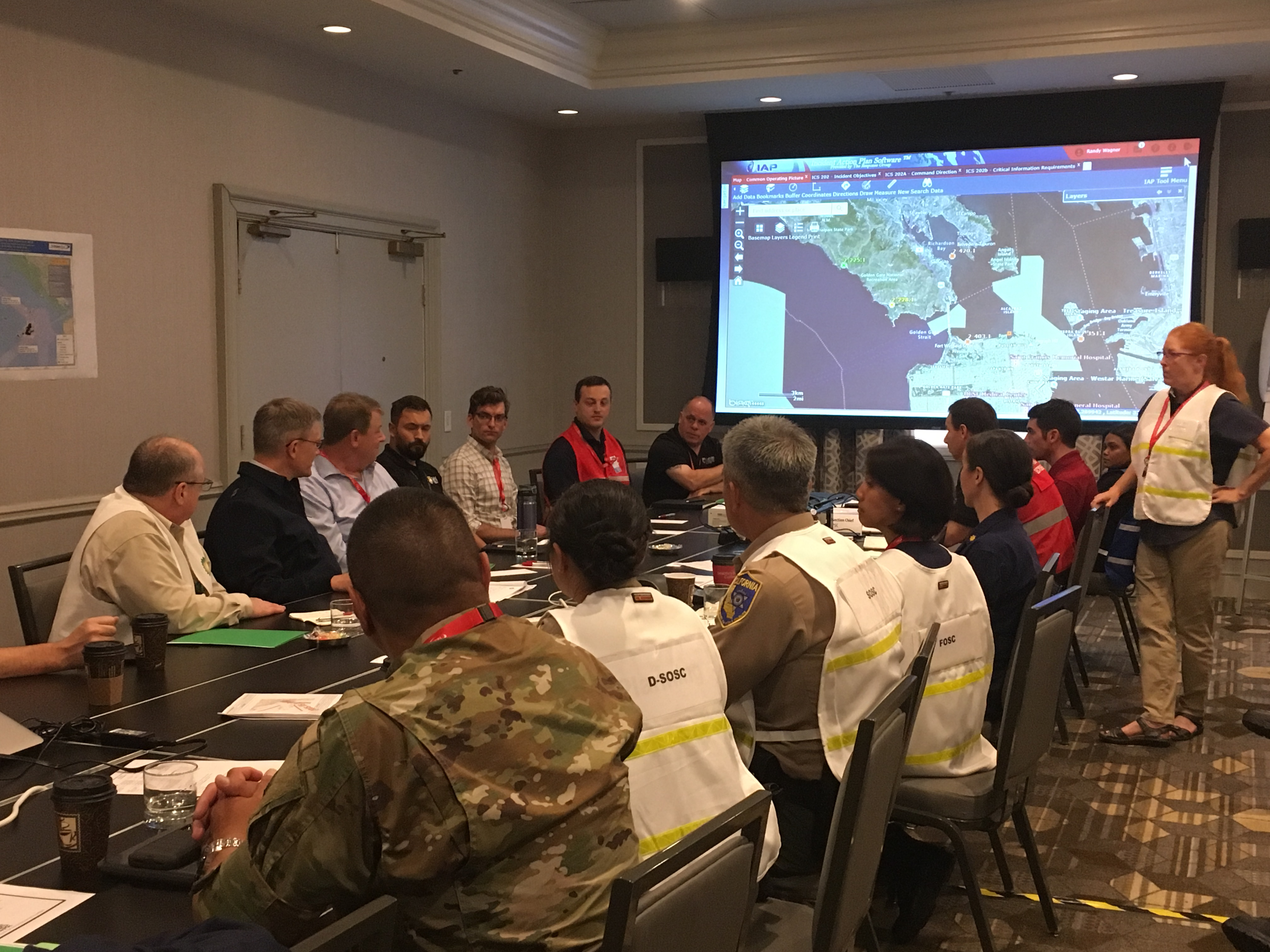 Agency officials in vests sitting at table with large map on screen.