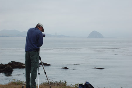 A CDFG scientist using a telescope to search for sea otters