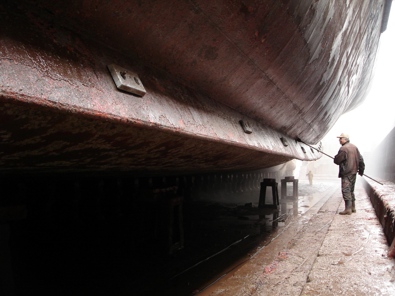 Ships hull getting cleaned in dry dock