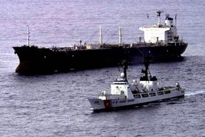 Anoil tanker being escoretd by a US Coast Guard Cutter
