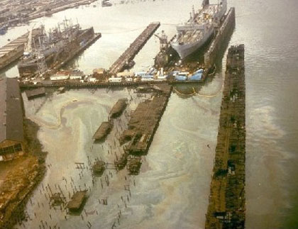 Several ships in dock with very heavy oil sheen on the water.