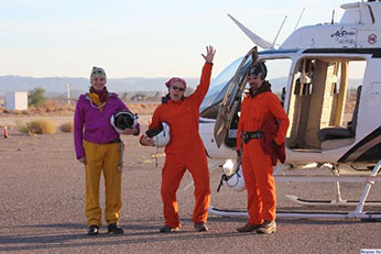 The desert bighorn crew smiles and poses for the camera in front of the helicopter they have used to survey sheep. They are wearing heavy, bright orange jumpsuits - link open in new window.