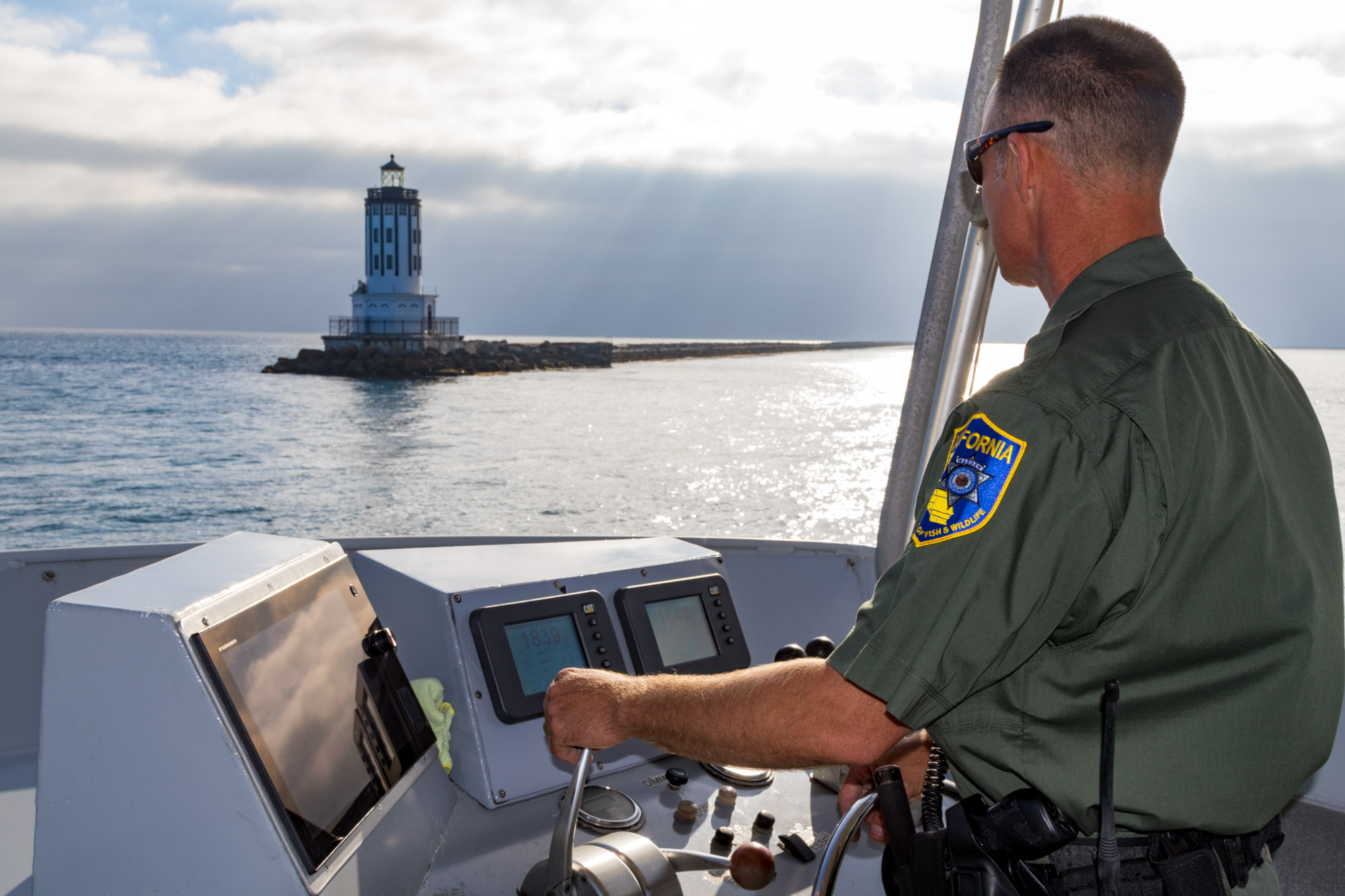 image of Wildlife Officer piloting a boat with lighthouse in background